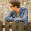 Hipster teenager with sunglasses over a fence — Stock Photo #53414985