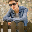 Hipster teenager with sunglasses over a fence — Stock Photo #53456603