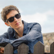 Hipster teenager with sunglasses over a fence — Stock Photo #53456967