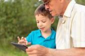 Barnbarn och farfar med en tablett utomhus — Stockfoto