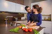 Paar umarmen und Vorbereitung von Gemüse in der Küche — Stockfoto