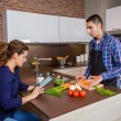 Man cooking and woman looking recipe in electronic tablet — Stock Photo #55056473