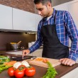 Man in home kitchen looking recipe with a electronic tablet — Stock Photo #55058555