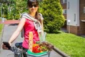 Young sportive woman with groceries in a basket bike — Stock fotografie