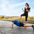 Girl coach training hard a man through push ups — Stock Photo #57373503