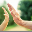 Child and senior man hands giving five in the nature — Stock Photo #58427465