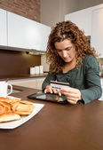 Woman with electronic tablet reviewing credit card payouts — Stock Photo