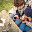 Young couple under blanket looking smartphone and eating muffin outdoors — Stock Photo #60135529
