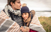 Young couple embracing outdoors under blanket in a cold day — Stock Photo