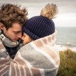 Young couple embracing outdoors under blanket in a cold day — Stock Photo #60202981