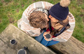 Young couple under blanket with hot drink kissing outdoors — Stock Photo