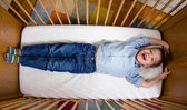 Happy boy lying in a cot with arms and legs stretched — Stock Photo