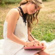 Romantic girl writing in a diary sitting outdoors — Stock Photo #60912685