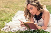 Romantic girl writing in a diary lying down outdoors — Stock Photo