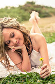 Romantic girl with flower in the hand lying down outdoors — Stock Photo