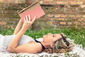 Romantic girl reading a book lying outdoors — Stock Photo