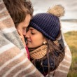 Young couple embracing outdoors under blanket in a cold day — Stock Photo #61879397