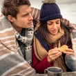 Young couple under blanket eating muffin outdoors in a cold day — Stock Photo #61882495