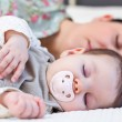 Young mother and her baby girl sleeping in the bed — Stock Photo #63391215