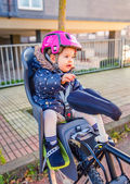 Little girl with helmet on head sitting in bike seat — Stock Photo