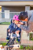 Father closing helmet to her daughter sitting in bike seat — Stock Photo