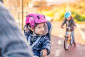 Lttle girl with helmet on head sitting in bike seat — Stock Photo