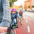 Lttle girl with helmet on head sitting in bike seat — Stock Photo #63594377