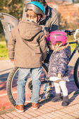 Children looking their father while repairing bicycle tire — Stock Photo