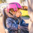 Little girl with helmet on head sitting in bike seat — Stock Photo #63630961