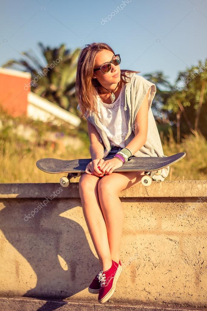 Jeune fille avec skateboard assis sur le mur en t photographie - Creer son skateboard ...