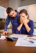 Desperate young woman with debts reviewing the bills — Stock Photo