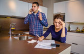 Angry man arguing at phone while woman calculating credit lines — Stock Photo