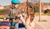 Young woman with child over bicycle on sunny day — ストック写真
