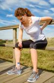 Athletic woman touching her back muscles by injury — Stock Photo