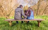 男と女のベンチに座っている少女を抱いて — ストック写真