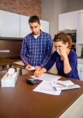 Unemployed husband reviewing the bills and wife crying by debts — Stock Photo