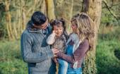Happy couple with daughter enjoying together leisure in the forest — Foto de Stock