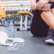 Sporty woman sitting with dumbbells, water and smartphone in gym floor — Stock Photo #70893993