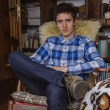 Young man with plaid shirt and jeans sitting on rocking chair — Stock Photo #71190363