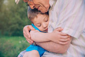 Happy grandson hugging to his grandfather outdoors — Stock Photo