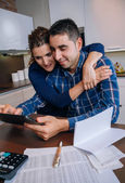 Cheerful couple using digital tablet at kitchen home — Stock Photo