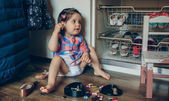Baby girl playing with hair clips sitting in the floor — Стоковое фото