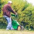 Senior man mowing the lawn with lawnmower — Stock Photo #72659995