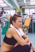 Vrouw met handdoek rusten in de sportschool na de training — Stockfoto