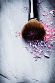 Makeup brush and crushed eye shadows — Stock Photo