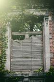 Old window with broken wooden shutters — Stockfoto