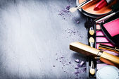 Various makeup products on dark background — Stock Photo