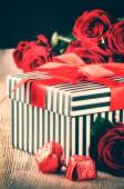 Valentine's setting with red roses and gift box — Stock Photo