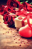 Valentine's setting with red roses and present — Stock Photo