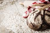 Baked bread loaf in rustic setting — Stock Photo